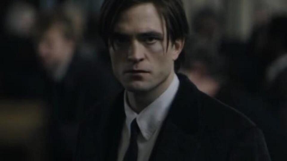 Un homme en veston-cravate dans un lieu public.
