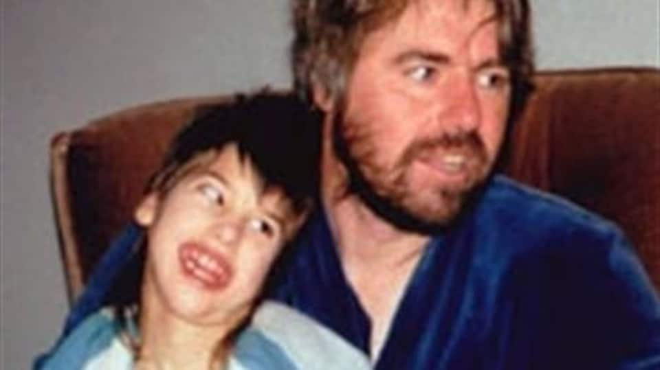 Robert Latimer tient sa fille Tracy sur ses genoux. Tous deux sourient en regardant vers la gauche.