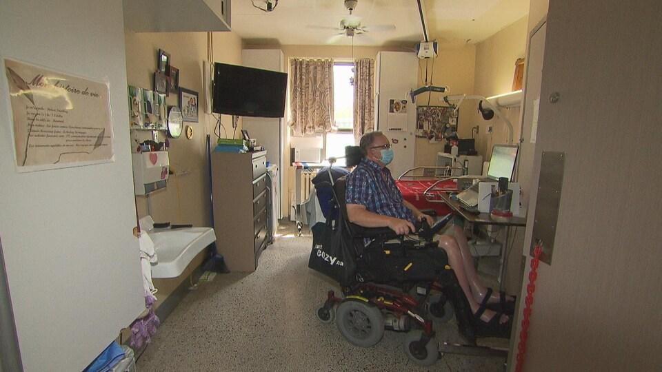Robert Tremblay, dans son fauteuil roulant, dans sa chambre.