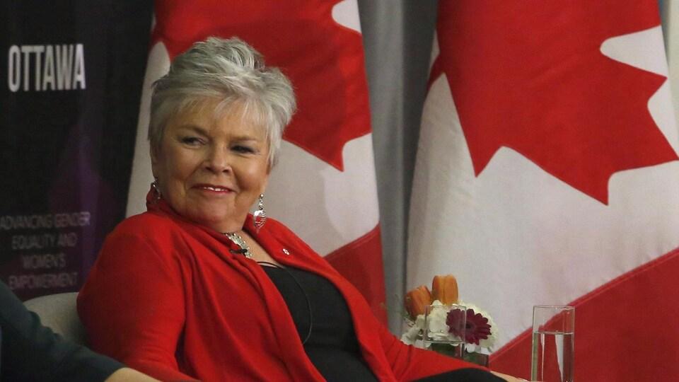 Roberta Jamieson est assise devant des drapeaux du Canada.