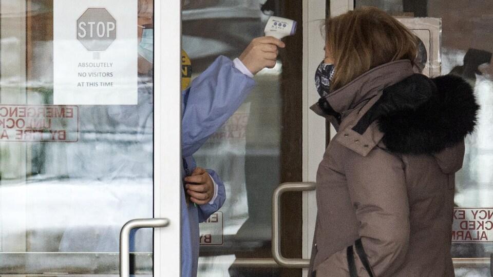 Une employée prend la température d'une femme à son arrivée dans un foyer de soins (archives).