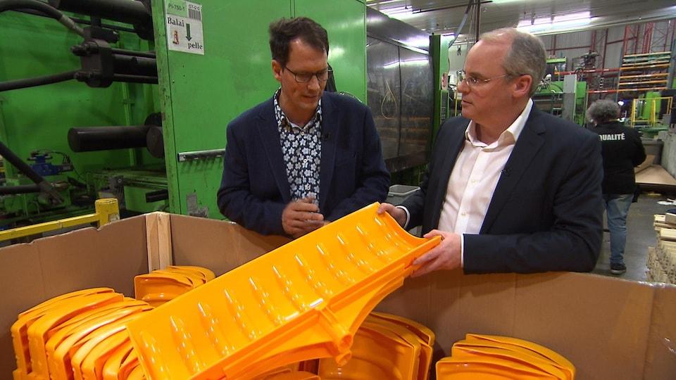 M. Belleville lui montre des pelles fabriquées dans son usine avec du plastique neuf.