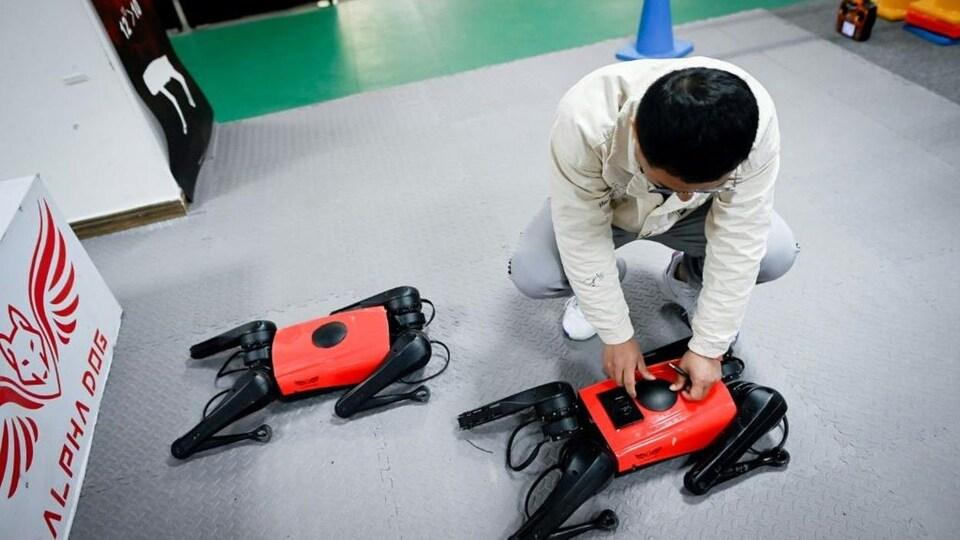 Un homme manipule des outils sur un robot-chien rouge au sol.