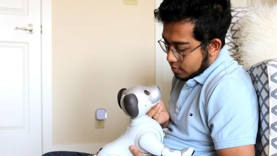 Rahatul Ananto avec un chien robot dans les mains