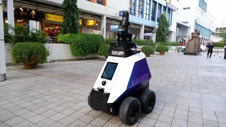 Un robot sur quatre roues circule dans un lieu public.