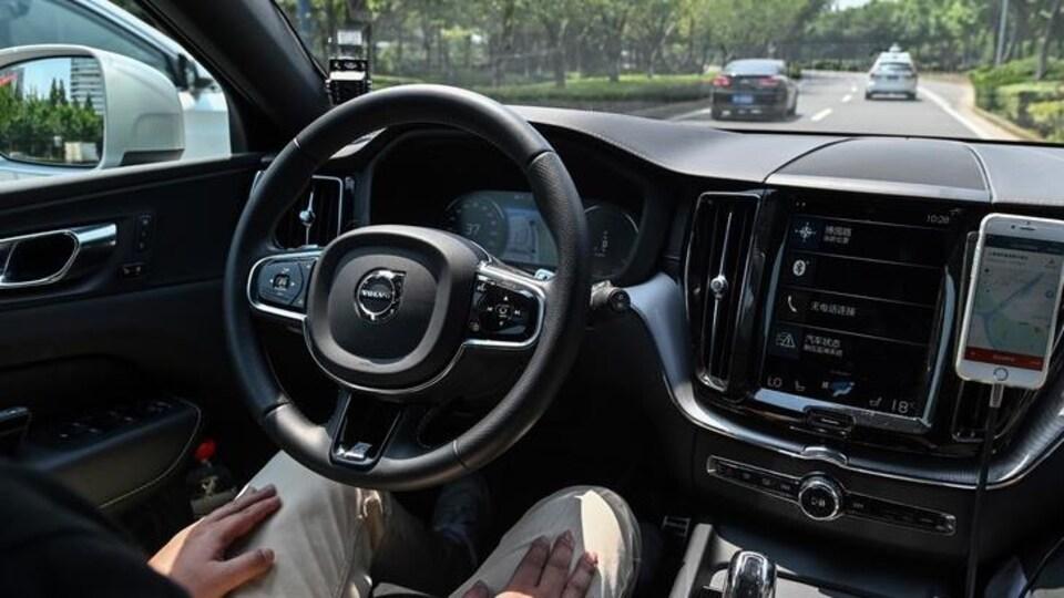 Intérieur d'une voiture autonome Volvo en marche sur une route.