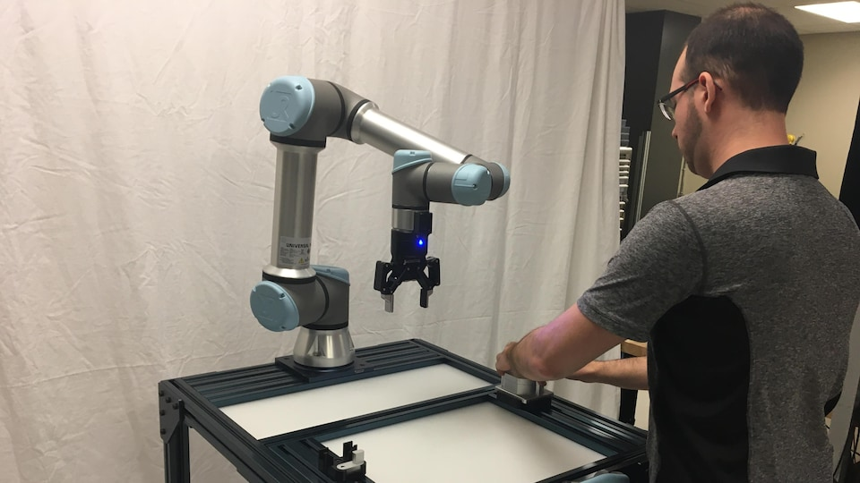 Un homme utilise un petit robot en forme de pince.