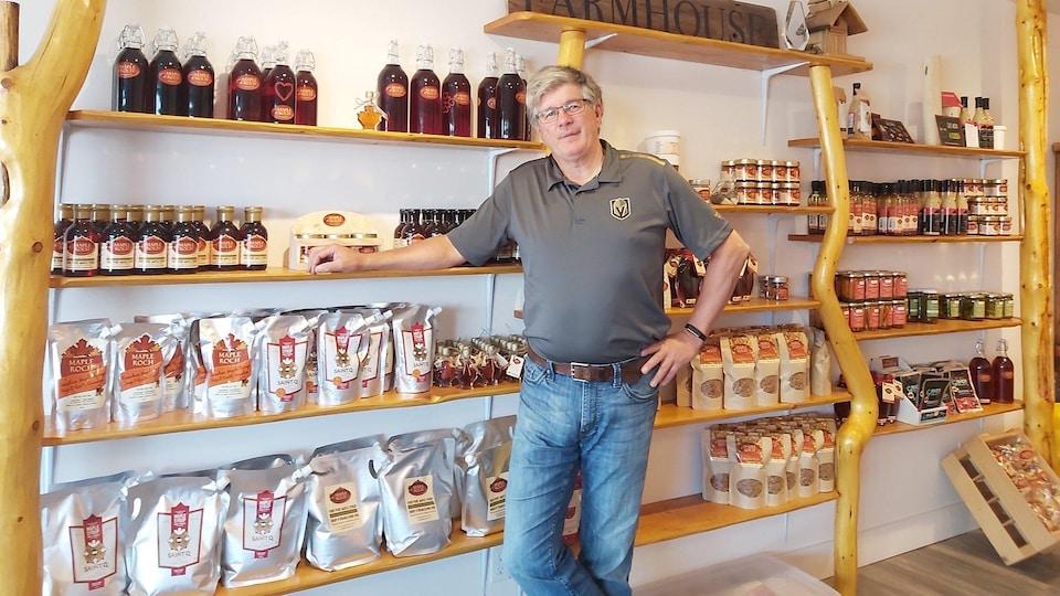 Roch Fortin debout devant les étagères de son magasin en Colombie-Britannique où il vend des produits de l'érable.