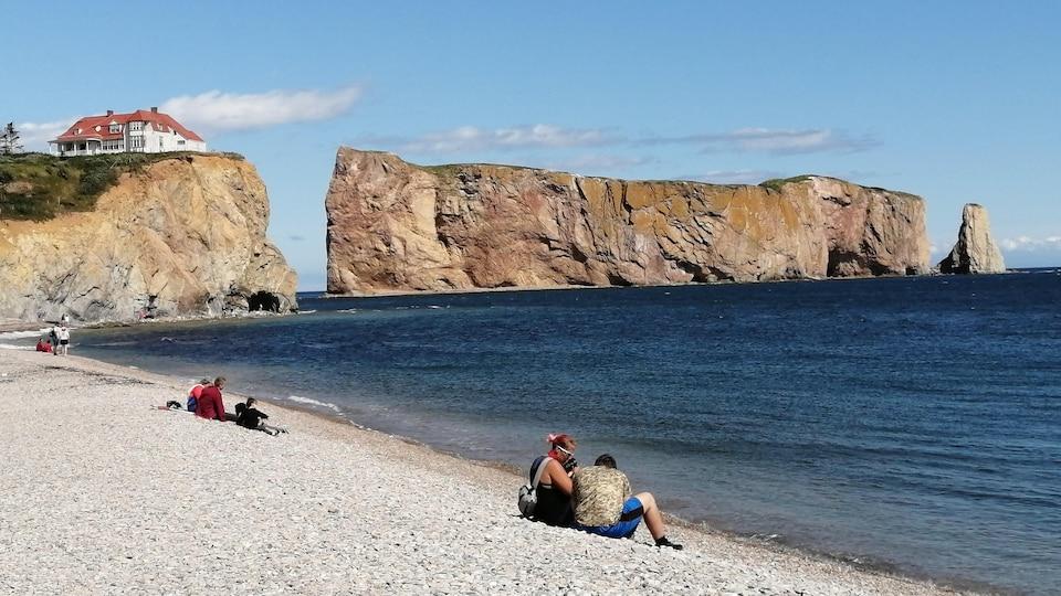Des touristes sont assis sur une plage de galets. À l'arrière-plan, on voit le Rocher Percé et un bâtiment patrimonial sur une colline.