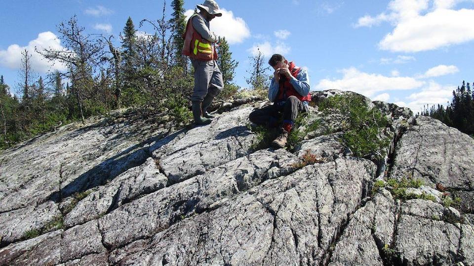Deux personnes sur une roche l'observent.