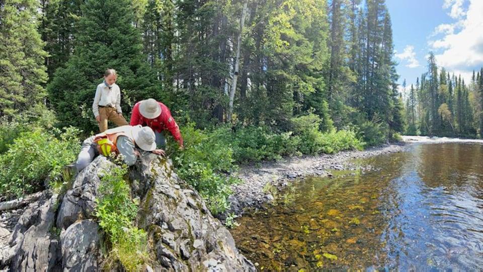 Trois personnes observent une roche sue le bord d'une rivière.