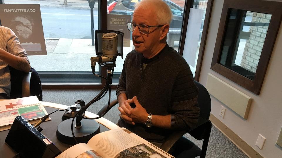 Roger Larivière en studio avec un livre à propos des champignons.