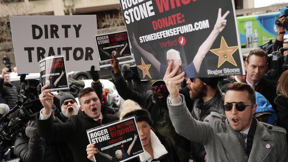 Des partisans de Roger Stone brandissent des pancartes sur lesquelles on peut lire : «Roger Stone n'a rien fait de mal». Sur une autre pancarte, on peut lire : «Sale traître».