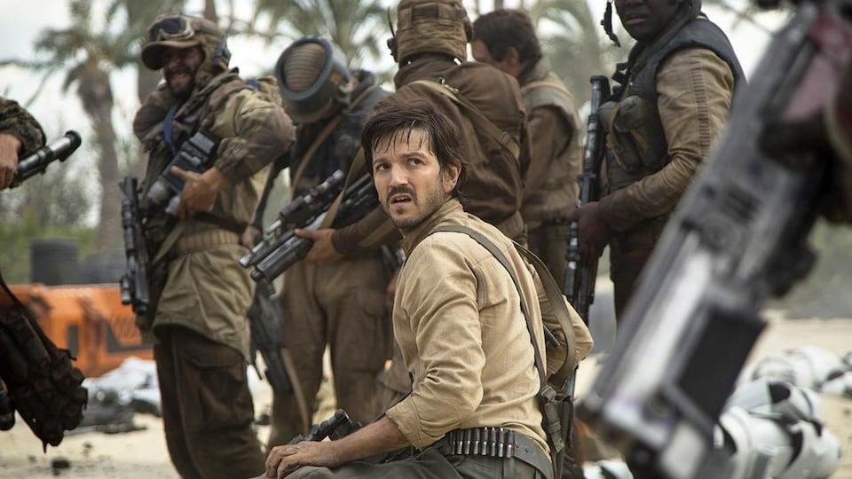 Diego Luna est agenouillé et regarde des soldats masqués qui passent devant lui. D'autres sont derrière lui.