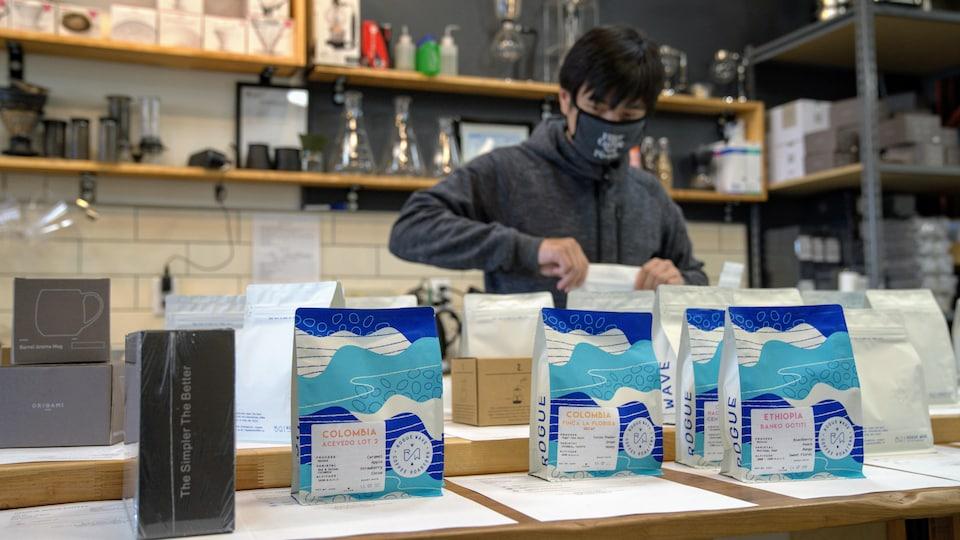 Un homme prépare des commandes dans un café.