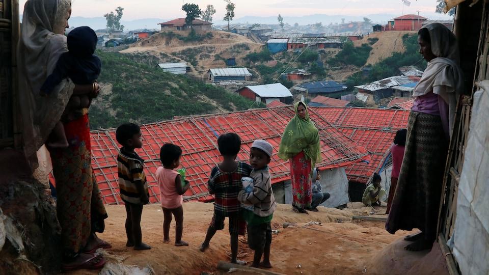Des enfants rohingyas se tiennent sur une butte qui surplombe un camp de réfugiés.