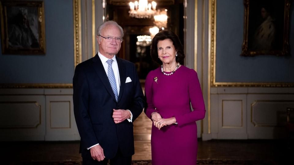 Carl XVI Gustaf et la reine Silvia, debout dans une salle du palais.