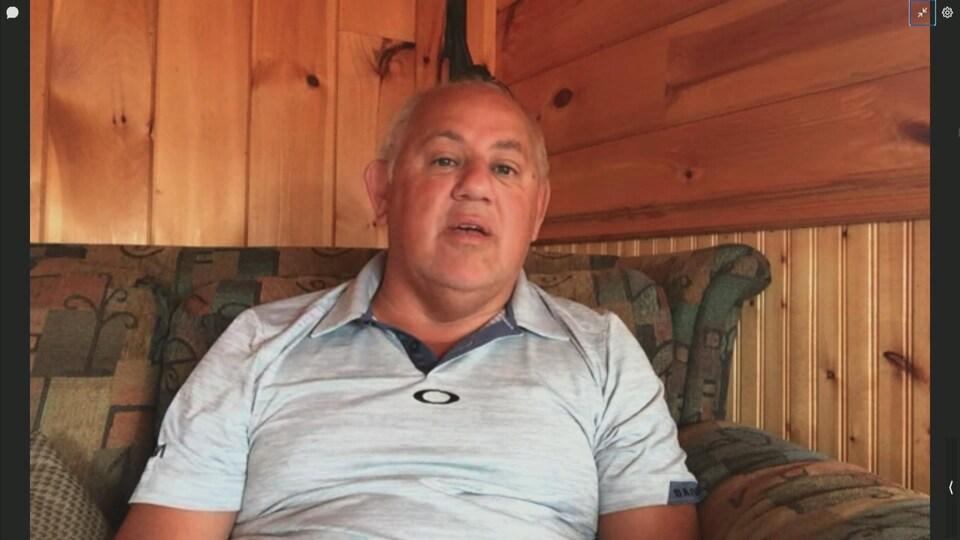 Un homme en entrevue par vidéoconférence.
