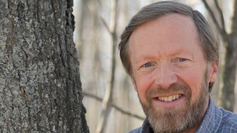 Un homme en chemise carrelée debout contre un arbre