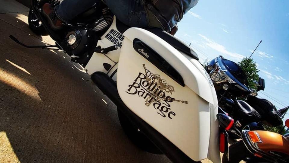 Un motocycliste qui participe au Rolling Barrage. Sa moto porte les couleurs de l'événement.