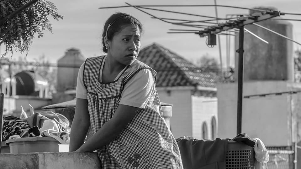 Une femme vêtue d'un tablier lave des vêtements dans un lavoir extérieur.