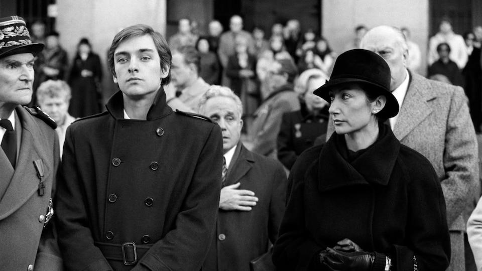 La femme regarde l'homme triste, dont le regard est lointain.