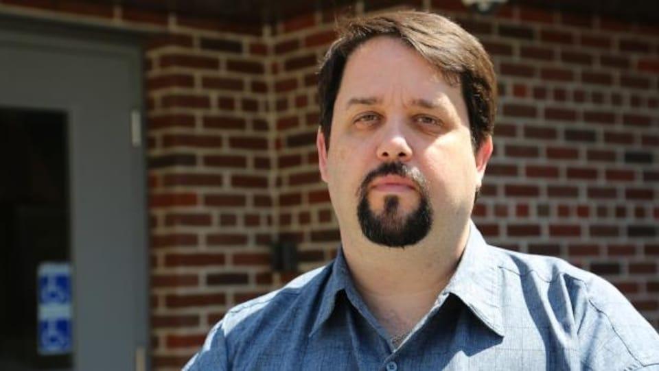 Un homme avec une barbe en beigne fixe la caméra très sérieusement.