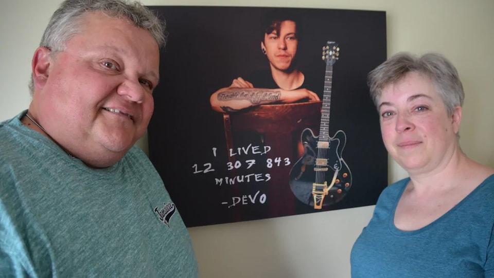 Ron et Holly Lachance pose à côté d'une photo de leur fils Devon.