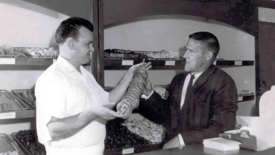 Photo en noir et blanc de Ron Joyce et Tim Horton dans un magasin de beignes.