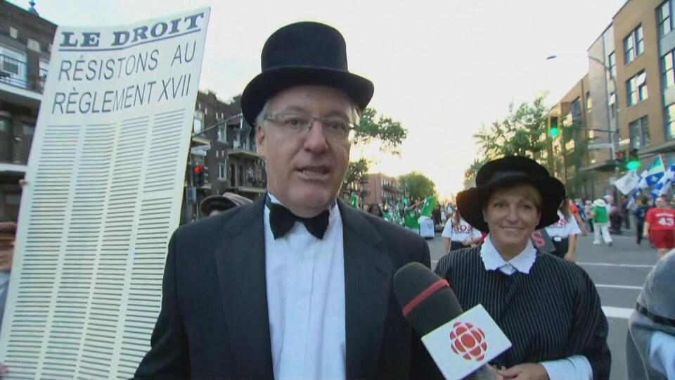 Un homme avec un chapeau haut-de-forme et une femme en costume d'époque