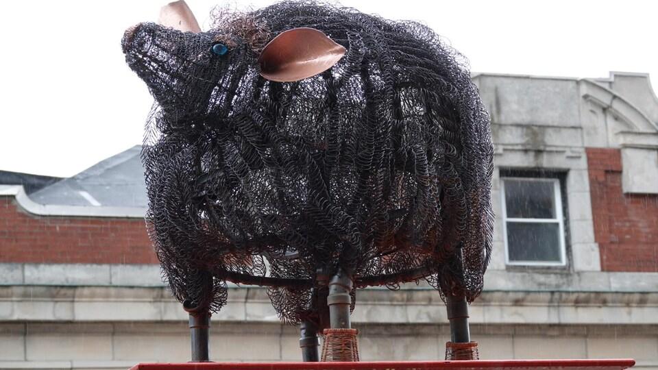 Une sculpture représentant un animal faite de cylindres de fer.