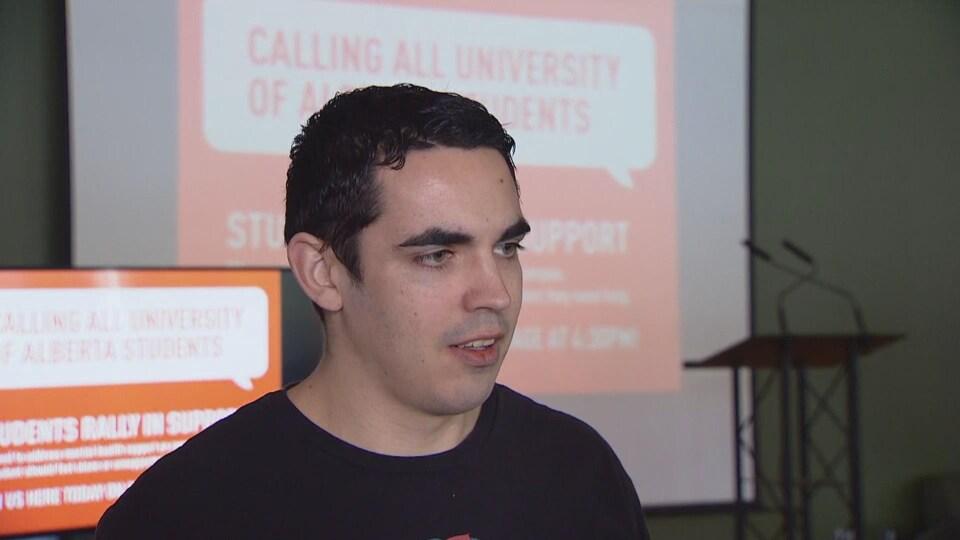 L'étudiant regarde à droite de la caméra. Derrière lui, un micro sur un podium.