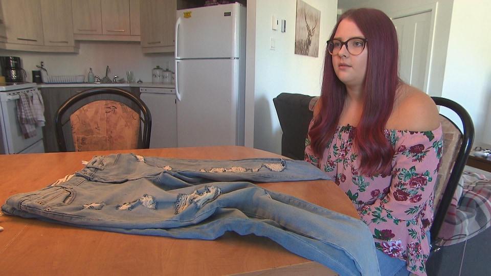 Une jeune femme qui présente la différence des tailles entre sa vieille paire de jeans et la nouvelle.