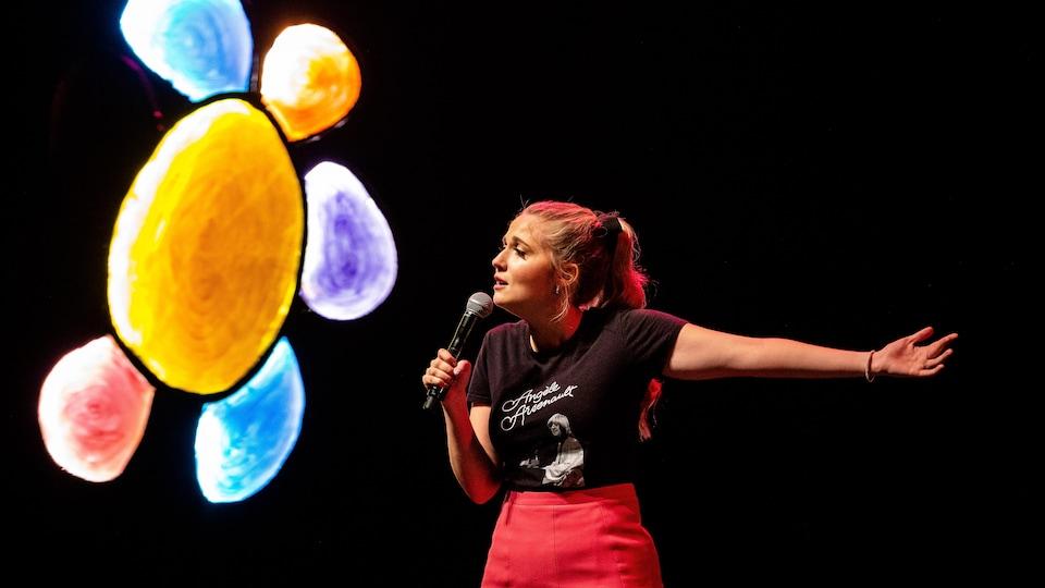Une femme, micro à la main, présente son spectacle d'humour.