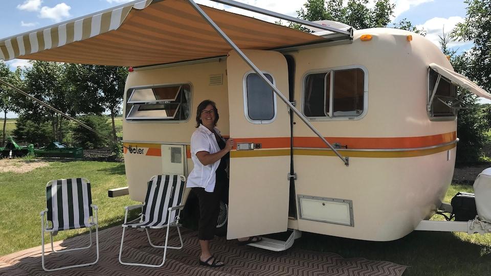 Une dame entre, tout sourire, dans sa caravane. Deux chaises de camping sont placées devant la caravane.