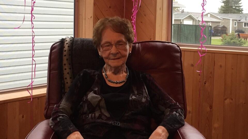 Une femme âgée assise dans un fauteuil tenant un certificat