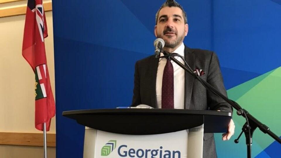 Un homme debout derrière un podium
