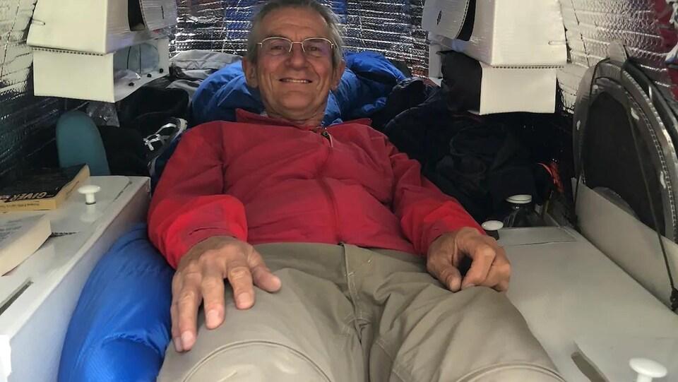 Un homme couché dans un abri allongé qui évoque la forme d'un cocon.