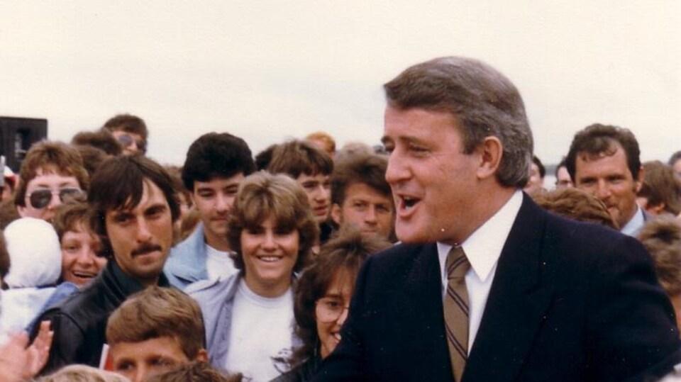Sur une photo d'archive, Brian Mulroney serre des mains dans une foule compacte