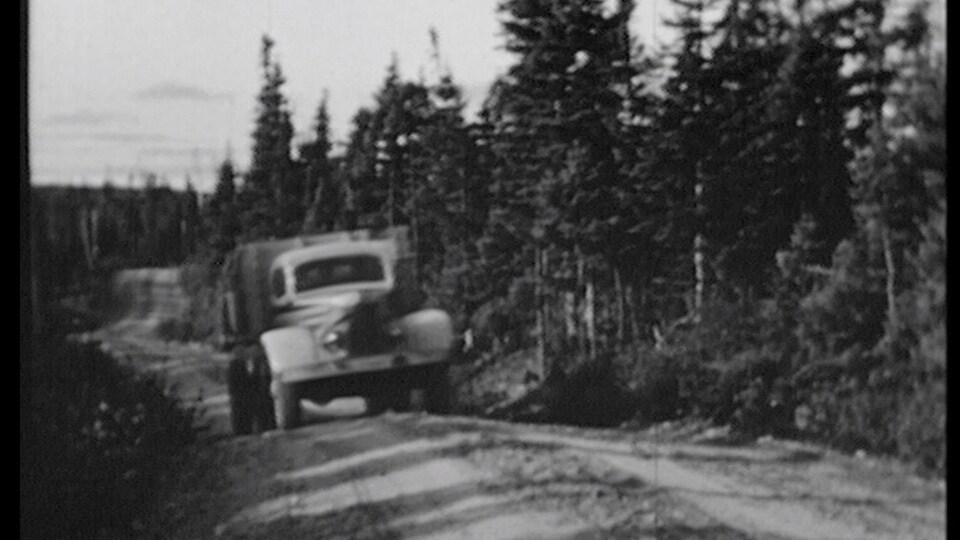 Une photo d'archive présente une vieille automobile circulant sur un chemin de terre en pleine nature.