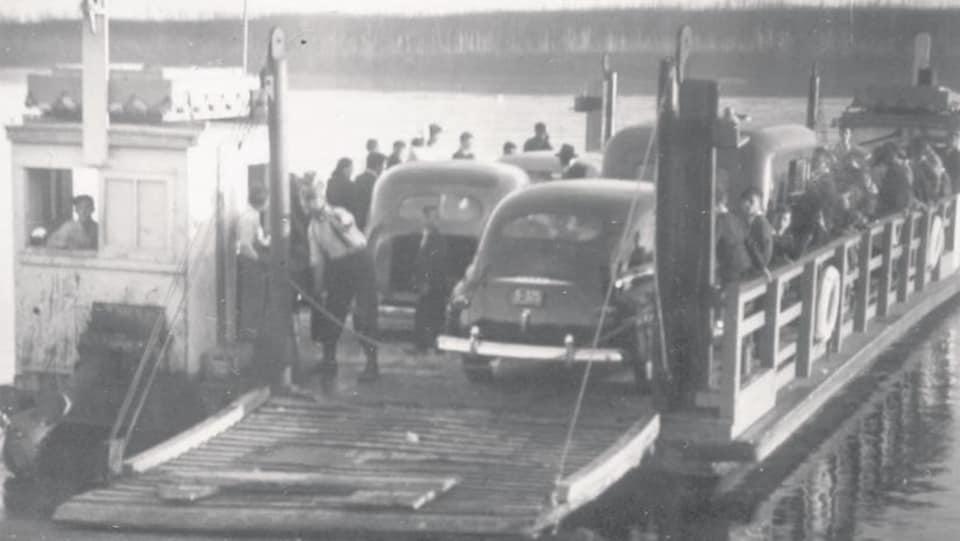 Une photo d'archive où l'on voit de vieux véhicules sur ce qui semble être un pont de bois.