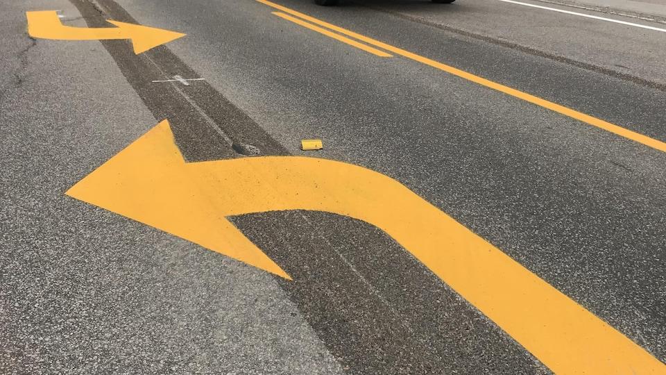 Une camionnette circule sur une route où des flèches ont été peintes dernièrement.