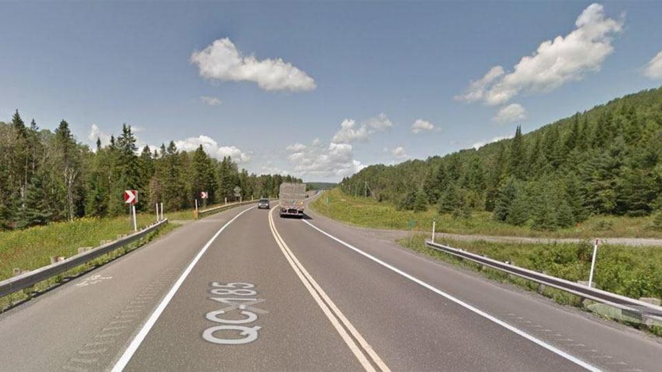 Un camion et une voiture se croisent sur la route en été.