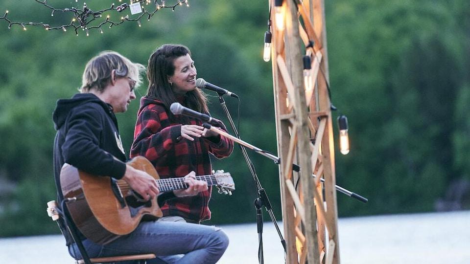 Un chanteuse et un homme avec une guitare font une prestation sur un quai flottant au milieu d'un lac.