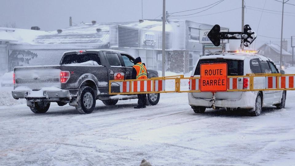Un camion de Transports Québec ferme la route à Matane. Le conducteur discute avec un automobiliste.