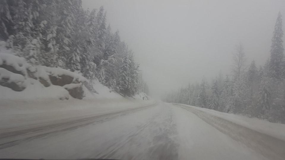 Route enneigée lors d'une tempête de neige dans les Rocheuses.