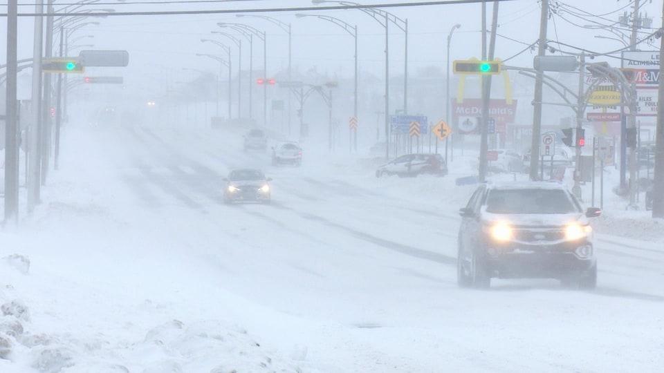 Des automobiles circulent dans la tempête au centre-ville de Matane.
