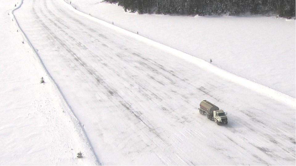 Un camion-citerne circule sur une route de neige et de glace au milieu au milieu d'une grande étendue de neige et de sapins.