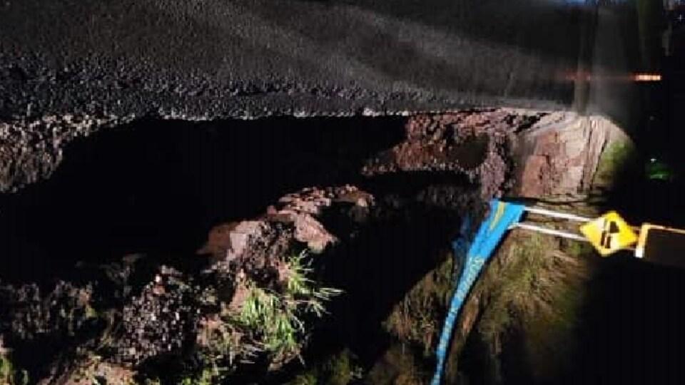 Une route effondrée durant la nuit.
