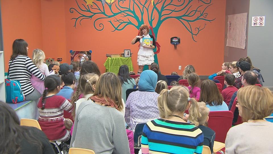Féeli Tout montre un livre à une petite foule d'enfants accompagnés de leurs parents